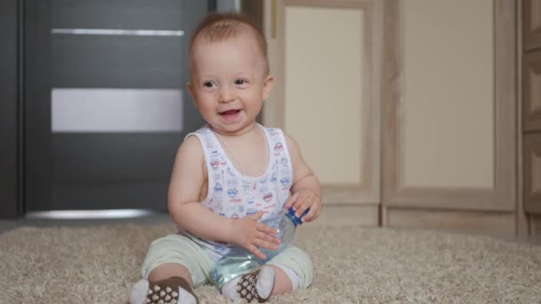Baby boy holds water bottle sitting at carpet at home.