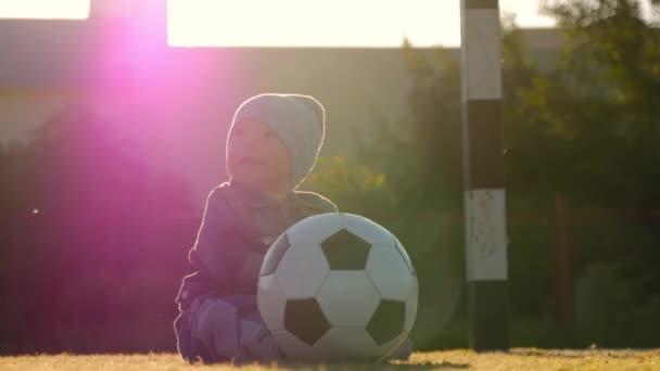 Mosolygós kisfiú egy futball-labdát a focipálya. Portréja egy kisgyermek ül a stadionban a labdát. Jövő futball sztár. Labdarúgás képzés koncepciója.