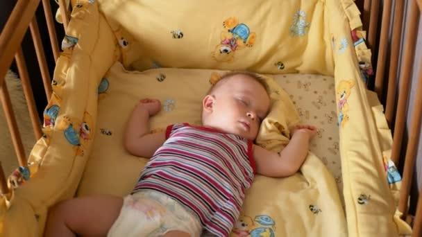 Egy kis baba fiú alszik, baba kiságy fekvő közelről.