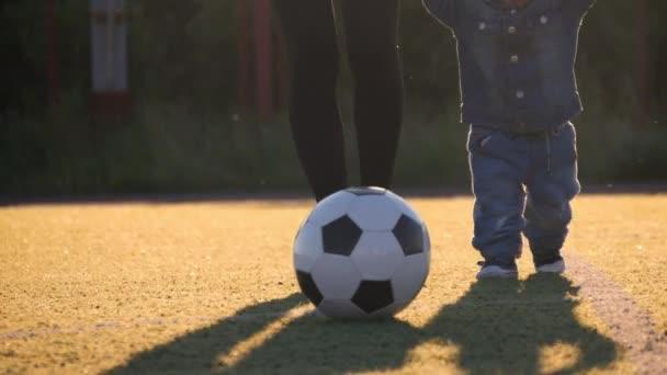 Malý chlapeček a jeho matka hraje s fotbalovým míčem na fotbalové hřiště.