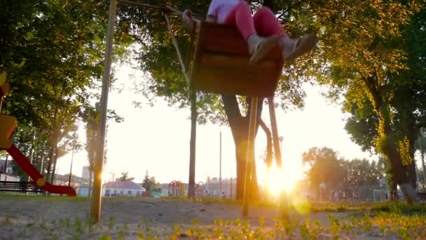 Smiling little girl swaying on swing at golden summer sunset. Fun in park, in woods, in nature. A warm summer day.