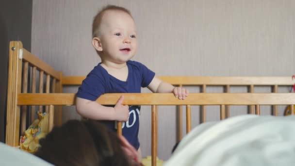 Babys stojící v dětské postýlce doma. Malý chlapec, naučit se stát ve své postýlce. Matka spí