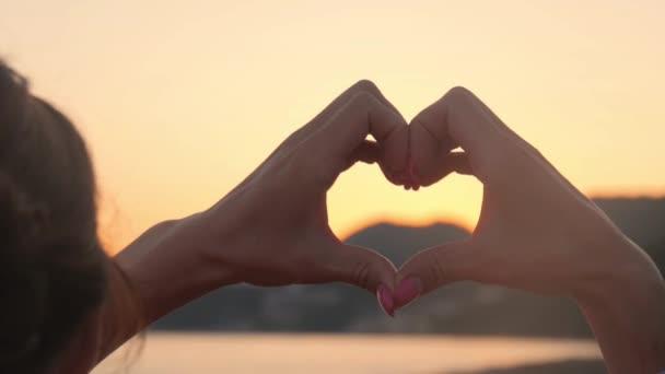 Alkotó egy szív alakú sziluettje naplemente kezek. Óceán nap átszűrődő szív alakú női kéz. szerelem. Természet. Remélem. Szabadság.