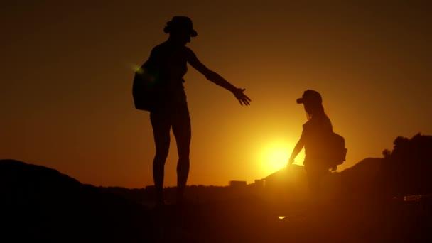Siluette della madre e del bambino turisti escursioni al tramonto. Mamma e figlia sulla vacanza di estate portando zaini. Bambina seguendo sua madre sul bordo della scogliera. Il concetto di viaggiare con i bambini