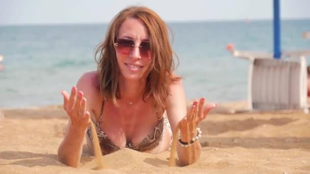 schöne Frau liegt am Strand und schüttet Sand aus ihren Händen. Strand glückliche Frau sonnt sich im Sand liegend lächelnd. schönes Mädchen ist im Sommerurlaub.