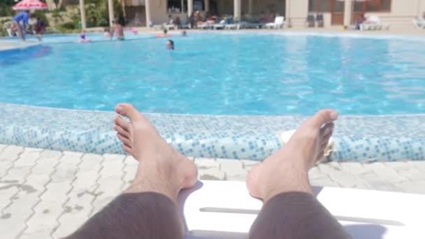 Užívat si letní dovolenou u bazénu, zblízka mužských nohou a vody u bazénu na letní slunečný den.