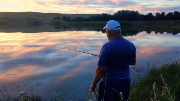 Rybář s rybářským prutem na břehu jezera při západu slunce. Muž ryby na návnadu