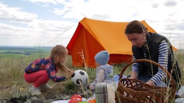 Rodiče a děti na pikniku a chtějí zůstat přes noc ve stanu. Cestovatel žena a děti relaxovat, hrát venku u stan. Rodinná dovolená, volný čas v lese.