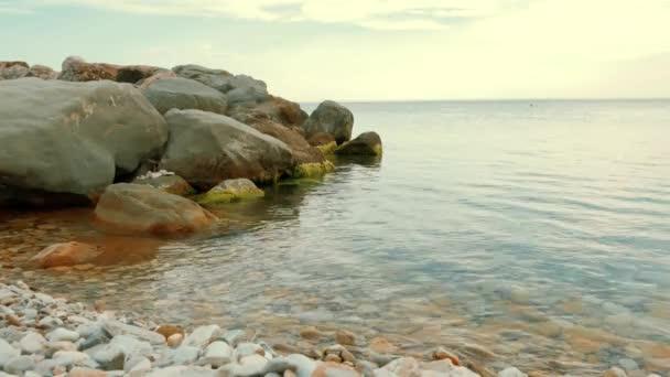Čelní pohled na mořské vlny tříštící se o skály. Rock s velkými kameny v moři a vlny s pěnou