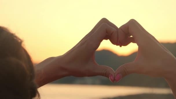 Ruce, tvořící tvar srdce s slunce silueta. Moře slunce svítí skrz srdce ve tvaru ženských rukou. Láska. Příroda. Naděje. Svoboda.