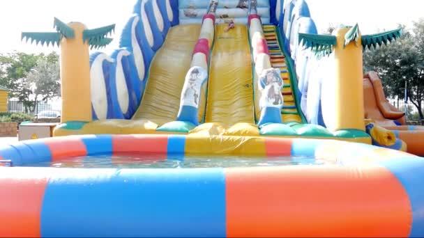 Girl sliding down on water slide in waterpark.
