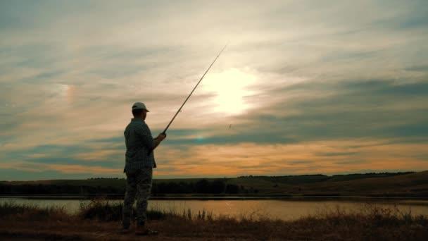 Silueta člověka těší rybolov s krásný západ slunce.
