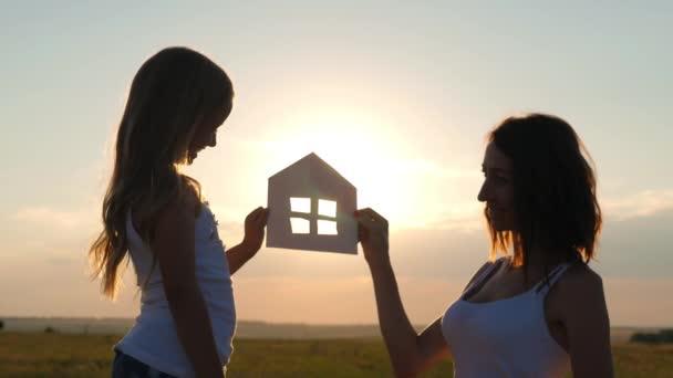Sziluett boldog anya és lánya álomházzal. Papírház, mint szimbólum. A családi boldogság fogalma.