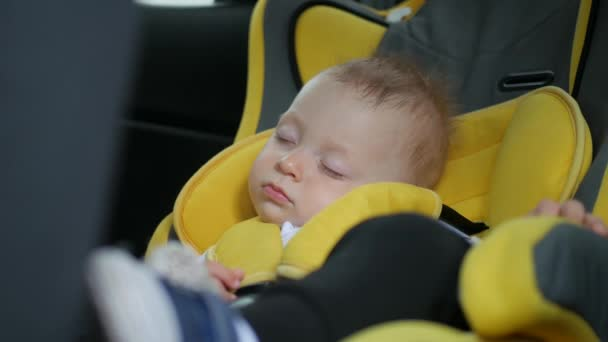 The baby sleeps in the car in the way. Sleeping child at back chair in car.