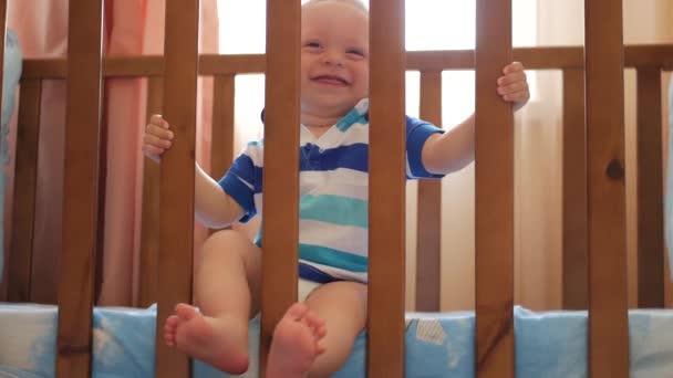 Dítě stojící v posteli doma. Portrét baby boyl stojí v postýlce. Dětské oči hledají matku.