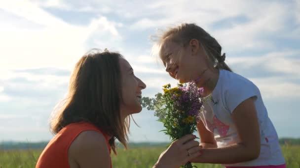 Mutter und Tochter in einem Blumenfeld. glückliche Familienmutter und Kindertochter haben Spaß an Blumen. fröhliche Tochter schenkt Blumenstrauß an ihre Mutter.
