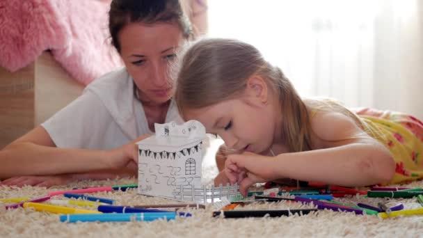 Mladá matka a její krásnou dceru, barvy papíru domu, ležící na podlaze doma, života, tvořivosti, vzdělání.