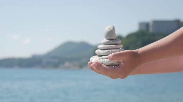 Pyramidy kameny leží na straně dětí na pozadí modré moře.