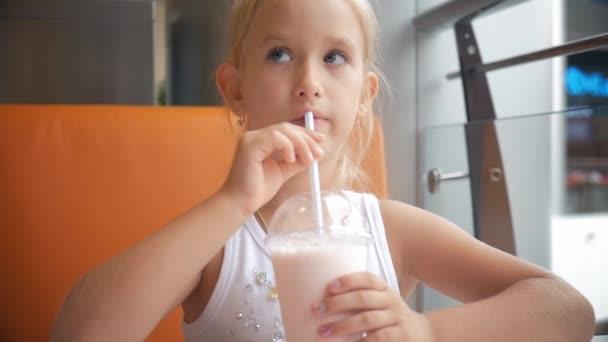Malé dítě dívka v kavárně pití mléka koktejl kakao s mlékem. Dětské nápoje, koktejl sedí v kavárně.