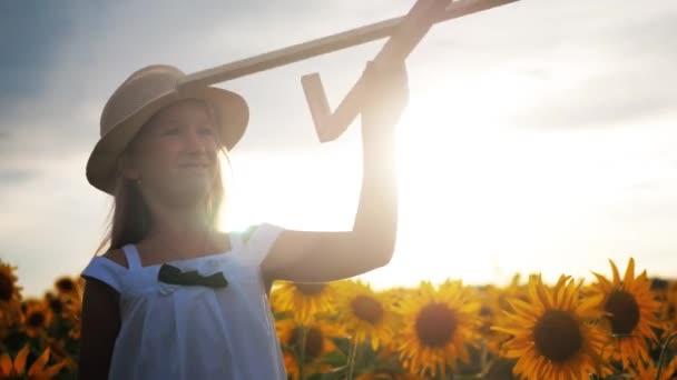 Egy lány kalapját, játszik egy fából készült repülőgép. Boldog gyermek játszó játék repülőgép a napraforgó mező a naplemente. A nap sugarai a hátsó nézet. Álom baba, a gyermekkor, a koncepció emlékek.