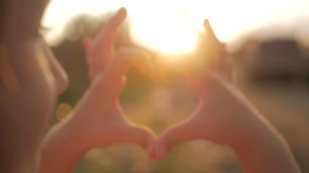 Holka dělá srdce ruce proti obloze, dítě rukama, tvoří tvar srdce s slunce silueta, láska, sen, léto