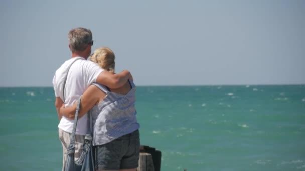 Zralý pár – objetí s výhledem na moře. Nádherný pár seniorů u vody. Staré šťastných lidí, drželi se za ruce venku. Soudržnost mezi starších lidí.