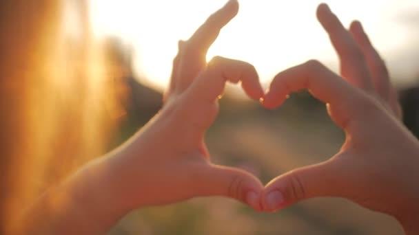 Lány csinál szív kezét az ég ellen, a gyermek kezét, alkotó egy szív alakú naplemente sziluett, szerelem, álom, nyáron