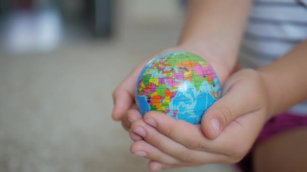 A gyerek a kezében tartja a földgömböt. Az utazás és a földi nyaralás fogalma.