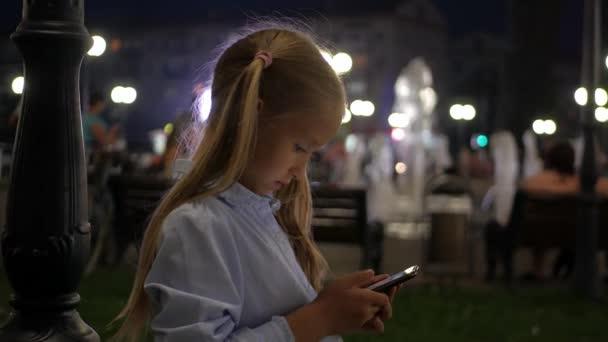 Teenager nutzt nachts Smartphone in der Stadt.