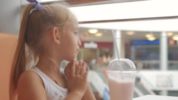 Malé dítě dívka v kavárně pití mléka koktejl kakao s mlékem. Dětské nápoje, koktejl sedí v kavárně