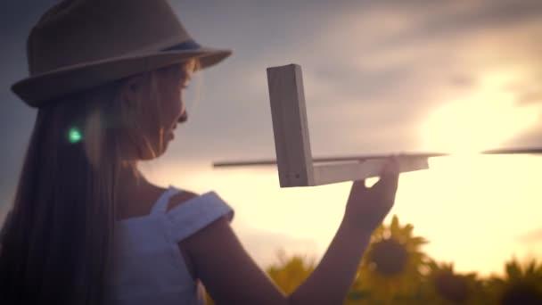 Egy lány kalapját, játszik egy fából készült repülőgép. Boldog gyermek játszó játék repülőgép a napraforgó mező a naplemente. A nap sugarai a hátsó nézet. Álom baba, a gyermekkor, a koncepció emlékek