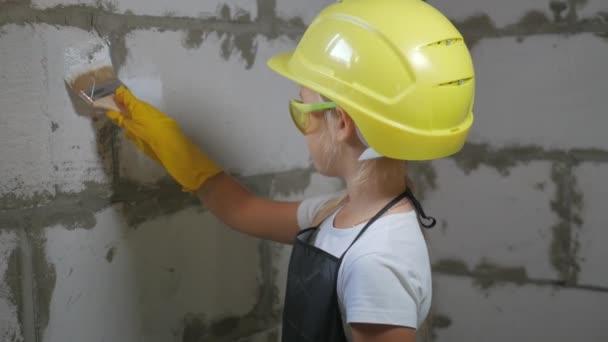 Kindheit, Bau, Architektur, Bau- und Personenkonzept - lächelndes kleines Mädchen mit gelbem Schutzhelm und Schutzbrille mit Pinsel für Farbe