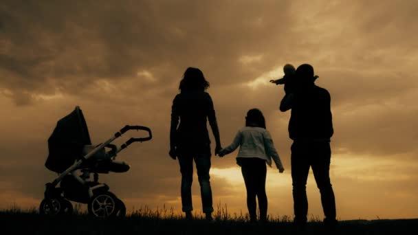 Siluette dei genitori felici avendo buon tempo con i loro bambini il allaperto al tramonto. Siluette dei genitori a piedi con i bambini piccoli con un passeggino e biciclette