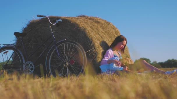 Mother and daughter in a field with hay stack in a sunny day. Family mom with cheerful daughter they came by bicycle in the field. Lifestyle, family holiday, outdoor, concept.