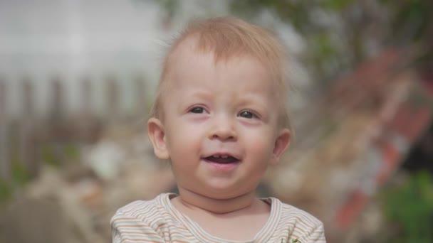 Rozkošný málo šťastný smích 1 rok starý chlapeček se dívá do kamery a úsměv.