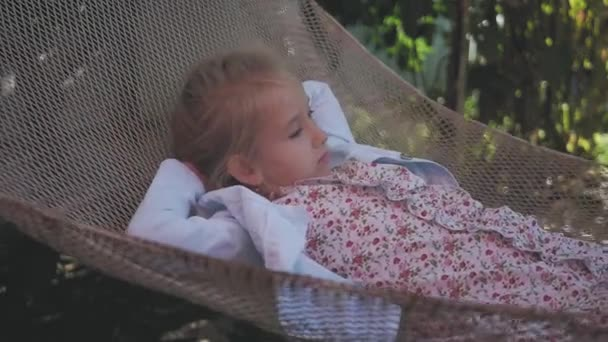 Cute child girl lying on hammock and relax at the garden.