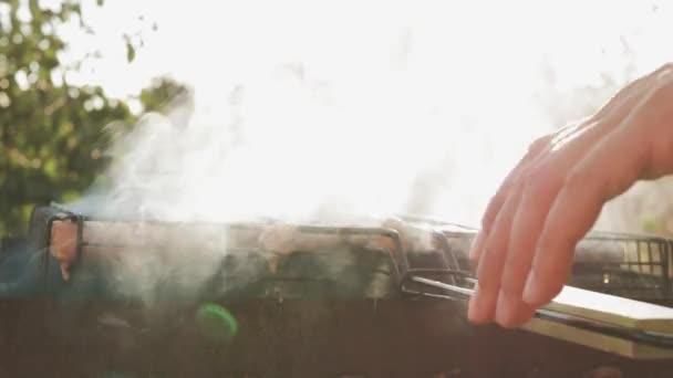 Grillezés a barbecue grill kolbász. A kolbász, hordozható grill grillezés sertéskolbászt közelről a grill, a hús és a tűz.