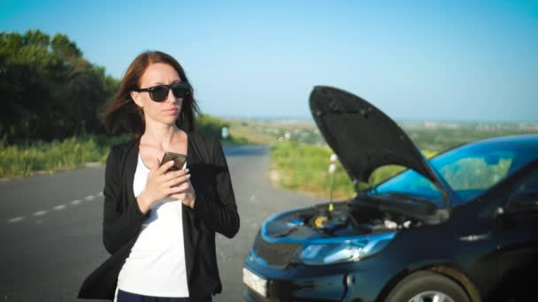 Woman near a broken car on the road is calling for assistance. Young worried girl is using a phone to explain the mechanic the problem with a car that she has.