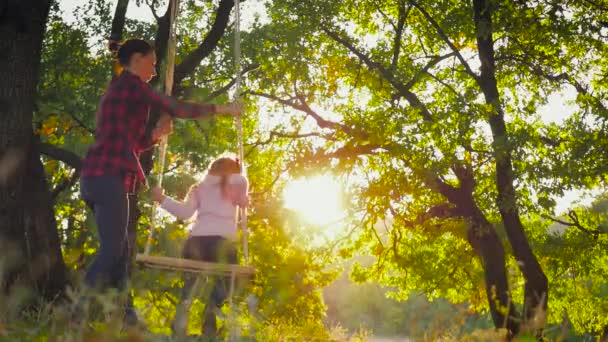Young mother and her child daughter swinging on the swings and laughing a autumn warm evening outdoors. Happy loving family.