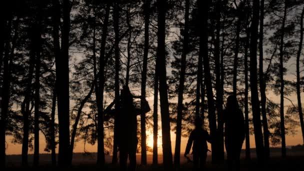 Siluette di padre, madre e figli escursionismo. Bambino si siede sulle spalle del padre. Backpackers di escursionismo trekking estate montagne. Giovane famiglia sulla vacanza di avventura di viaggio