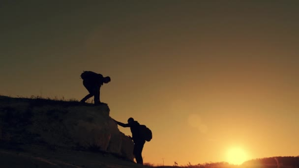 Silhouette einer helfenden Hand zwischen zwei Bergsteigern. Zwei Wanderer auf dem Gipfel des Berges, ein Mann hilft einem Mann, einen steilen Stein zu erklimmen. Wanderpaar hilft sich gegenseitig bei Sonneneinstrahlung in den Bergen.