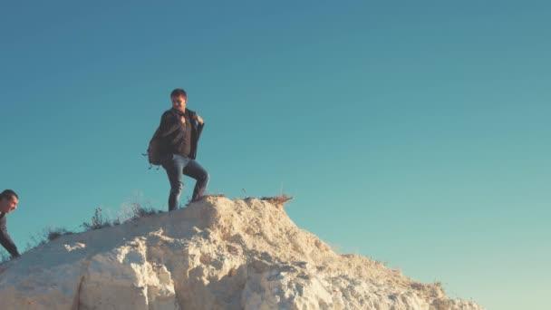 Lezec pomoci kolega stoupání, muž s batohem natáhl pomocnou ruku svého přítele. Tramp pomáhá přítel při pěší turistiku na kopci. Turistické muž pomáhá někdo vystoupit na horu.