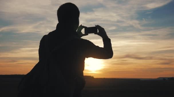 Silueta cestovatelů s fotografii západu slunce s telefonem. Léto, cestování a technologie pojmy.