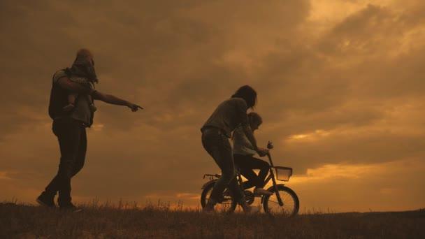 Siluette dei genitori felici avendo buon tempo con i loro bambini il allaperto al tramonto. Siluette dei genitori a piedi con i bambini piccoli con una bicicletta