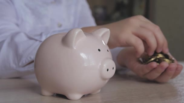 Boldog lány az ő otthonában malacka bank pénzt takarít. Gyermek, behelyezése egy érmét a piggy bank, fedett pénzügyi fogalom. Pénzt takaríthatunk meg a jövőbeni koncepció gyerek.