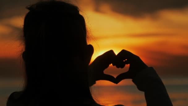 Young beautiful girl makes heart by her hands in heart shape framing setting sun at sunset over ocean. Emotional concept of happy exclusive lifestyle moment, sharing time, relaxing.