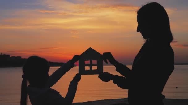 Silueta, malý papírový dům z lepenky se koná rukama proti západu slunce moře. Efektivitu a domácí koncept - zblízka z pálivých papriček papíru domu. Pojem úvěry na bydlení a hypoték