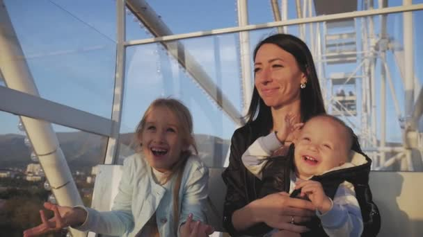 Young mother with children on a ferris wheel. The concept of vacation and travel.