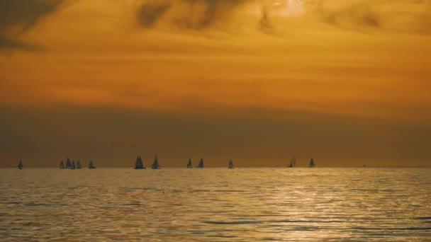 Vitorlások fehér vitorlák naplementekor. Gyönyörű kilátás nyílik a Vitorlás jachtok tengeri naplementekor.