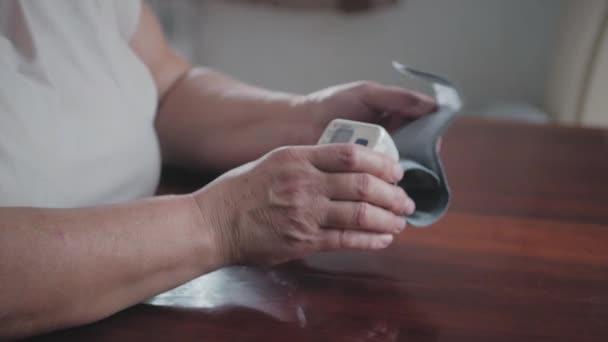 Starší obézní ženy měření tlaku s digitálním TLAKOMĔR zatímco sedí u stolu. Starší žena se stará o zdraví s krbu beat monitoru. Zdravotní péče a zdravotnické koncepce.